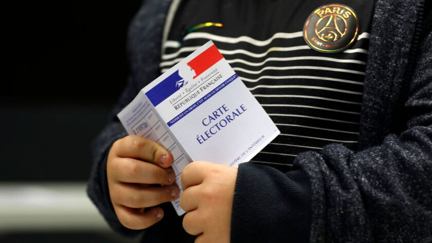 A child holds his mother's voting card on Sunday in Anthony, outside Paris.