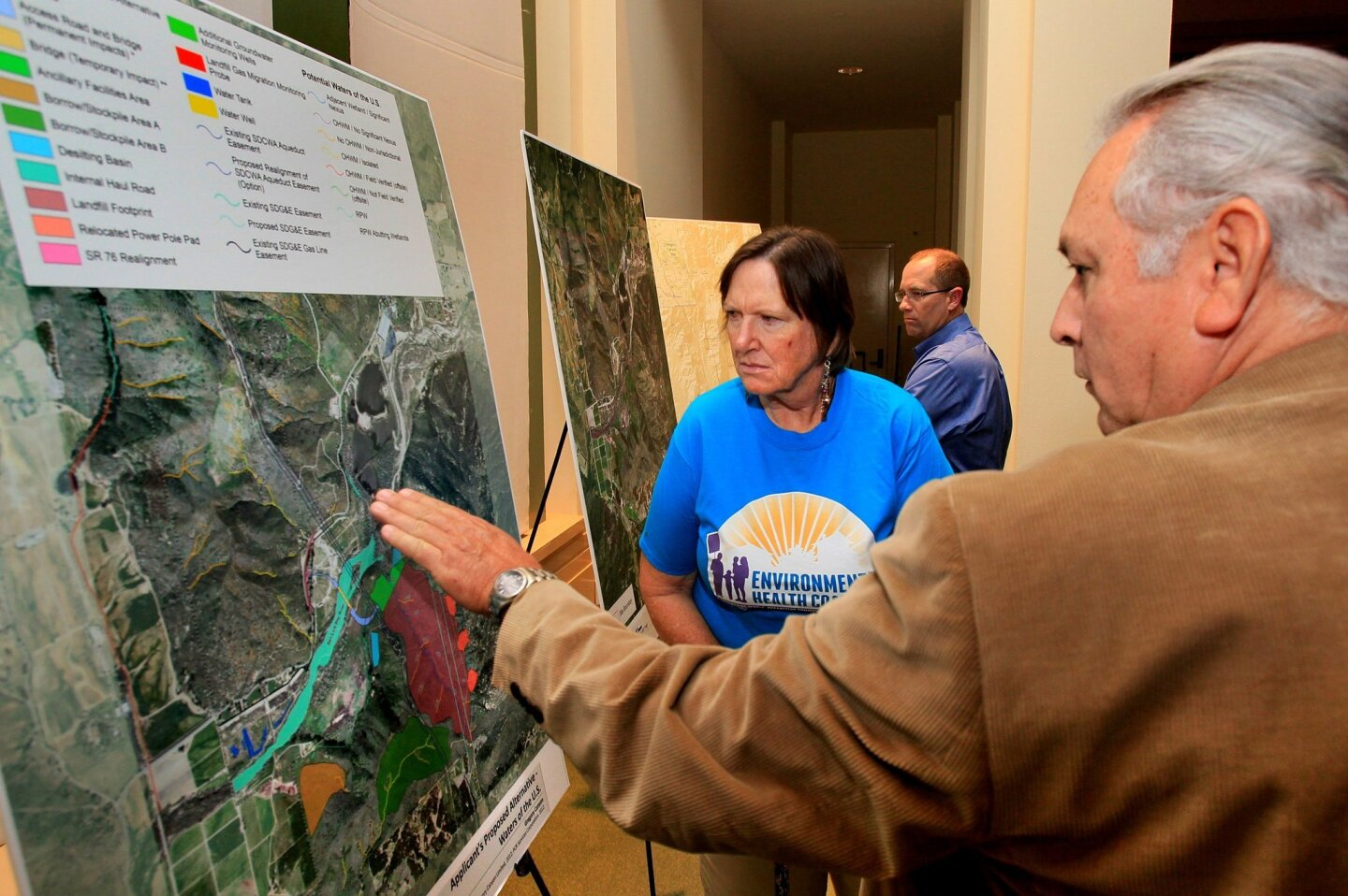 Prior to the U.S. Army Corps of Engineers public hearing concerning the Gregory Canyon Landfill project Debbie Westcott, of the Environmental Health Coalition, and Mel Vernon, Captain of the San Luis Rey Band of Mission Indians, look at a map of the project. Both oppose it.