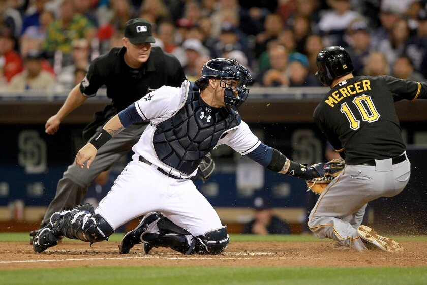 San Diego Padres catcher Yasmani Grandal is late with the tag on Pirates Jordy Mercer who scored on a Neil Walker single to rightfield in the top of the sixth inning. Mercer also had a solo home run earlier in the game.