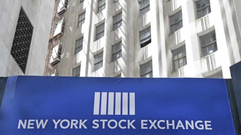 FILE- In this April 26, 2018, file photo, a sign promoting the New York Stock Exchange hangs above a