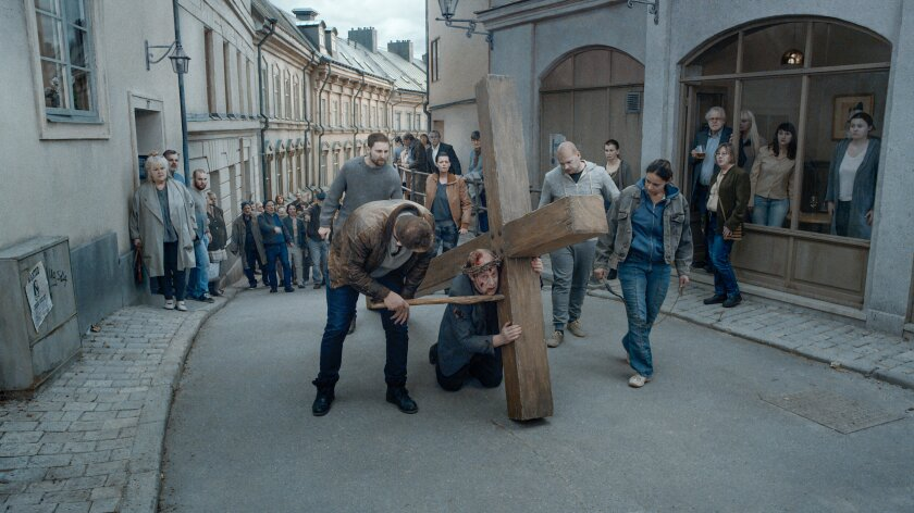 """A man carries a cross through a modern street in the movie """"About Endlessness."""""""