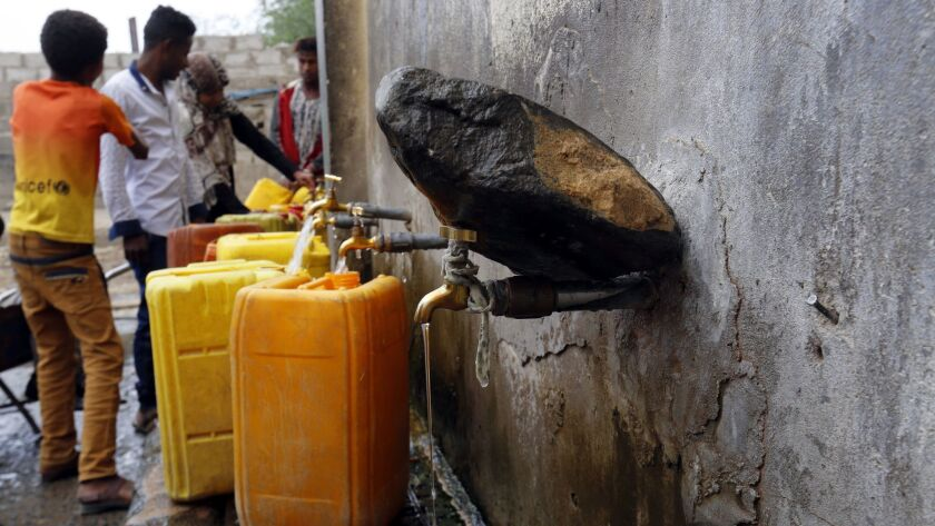 Yemenis fill jerrycans with drinking water in the Yemeni capital, Sana.