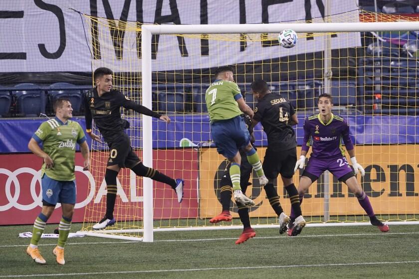 LAFC goalkeeper Pablo Sisniega watches as Seattle midfielder Cristian Roldan and LAFC defender Eddie Segura vie for the ball.