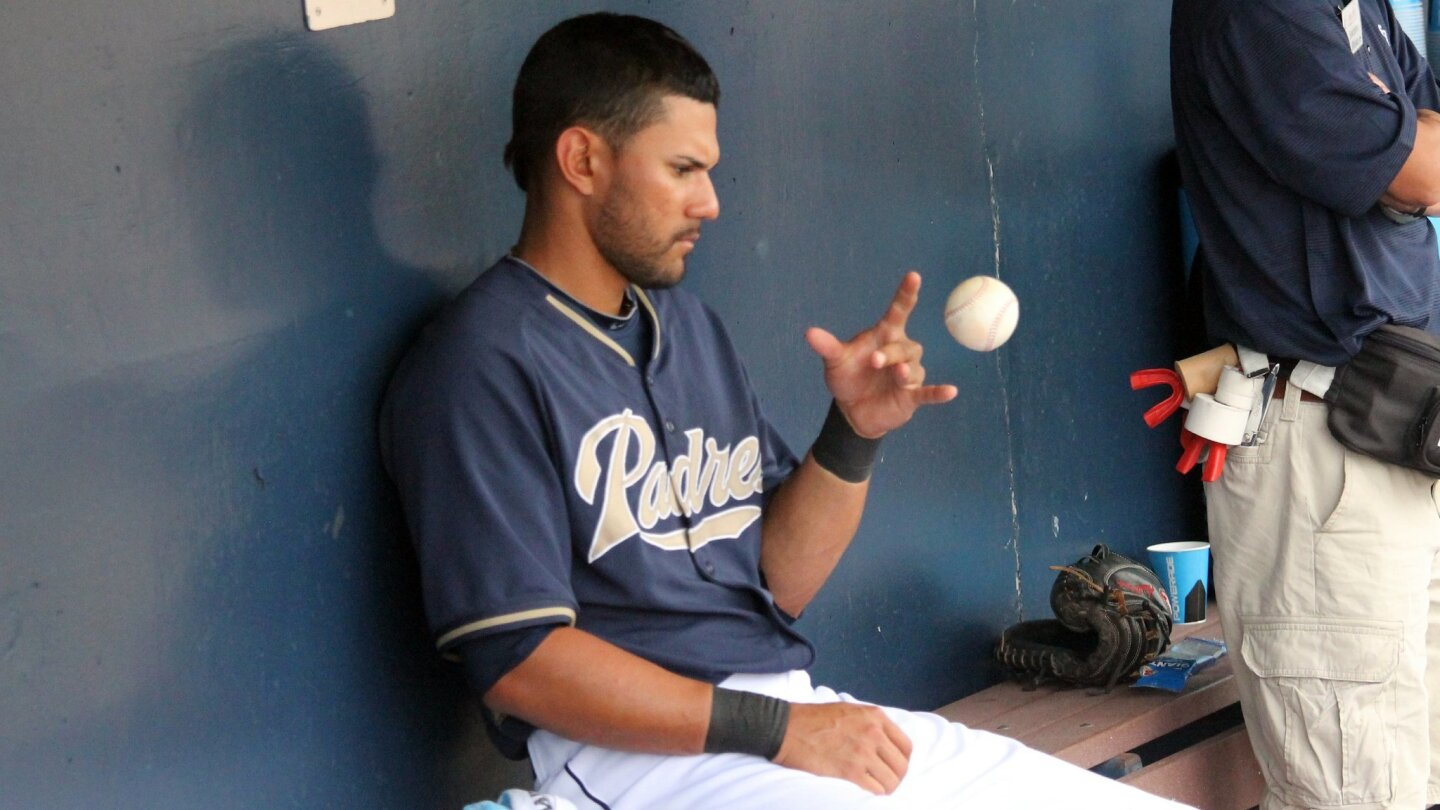Padres outfielder Reymond Fuentes plays around with a baseball in the dugout during spring training in Peoria, Ariz.