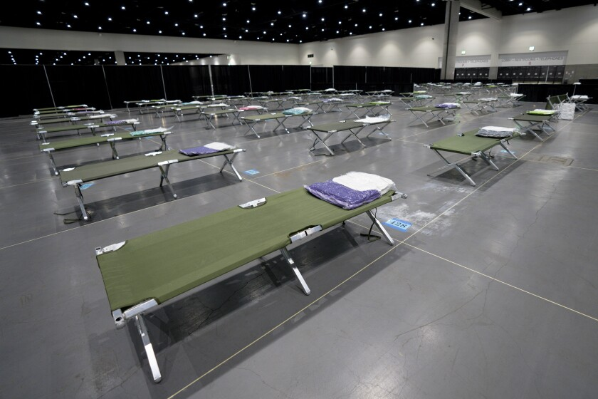 Rows of cots fill a room at the San Diego Convention Center