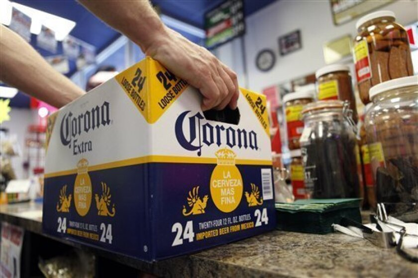 FILE - In this April 1, 2010 file photo, a customer places a case of Corona Extra on the checkout counter for purchase at Susquehanna Beer and Soda in Marysville, Pa. The maker of Robert Mondavi wine and Svedka vodka posted a $279.8 million fourth-quarter profit Thursday, April 7, 2011, reversing a year-ago loss, as it saw a double-digit rise in wine sales in North America. (AP Photo/Carolyn Kaster)