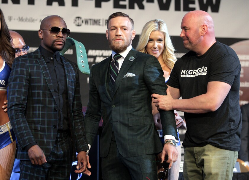 UFC president Dana White grabs Connor Mcgregor's arm as he poses with Floyd Mayweather Jr. during a news conference Aug. 23, 2017 at the MGM Grand.