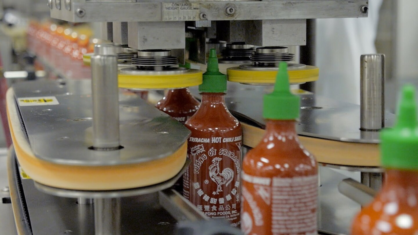 Sriracha bottles on a conveyor belt at the Huy Fong Foods facility in Rosemead are shown.