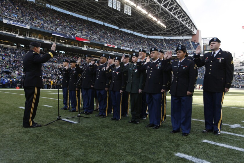 "Washington National Guard members reenlist before an NFL game between the Seattle Seahawks and the Minnesota Vikings. Such events have come under criticism as ""inappropriate and frivolous."""