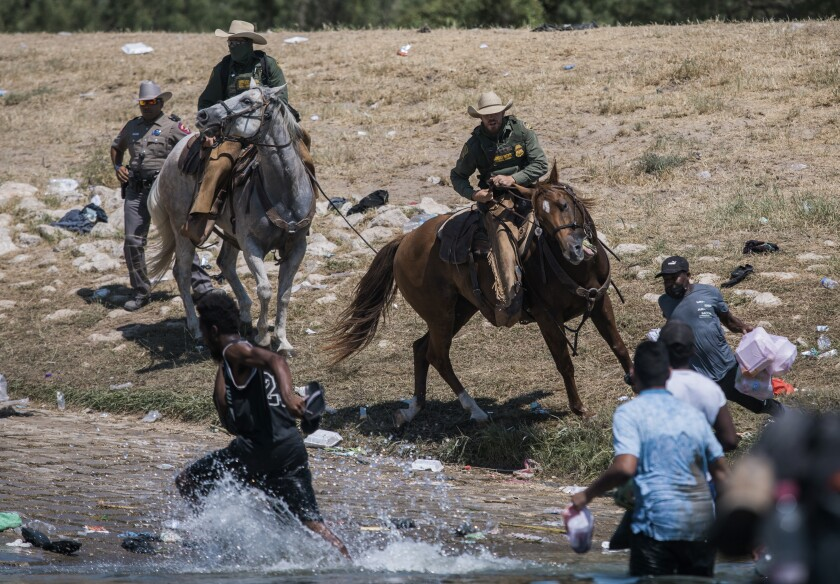 U.S. Customs and Border Protection mounted officers attempt to contain migrants