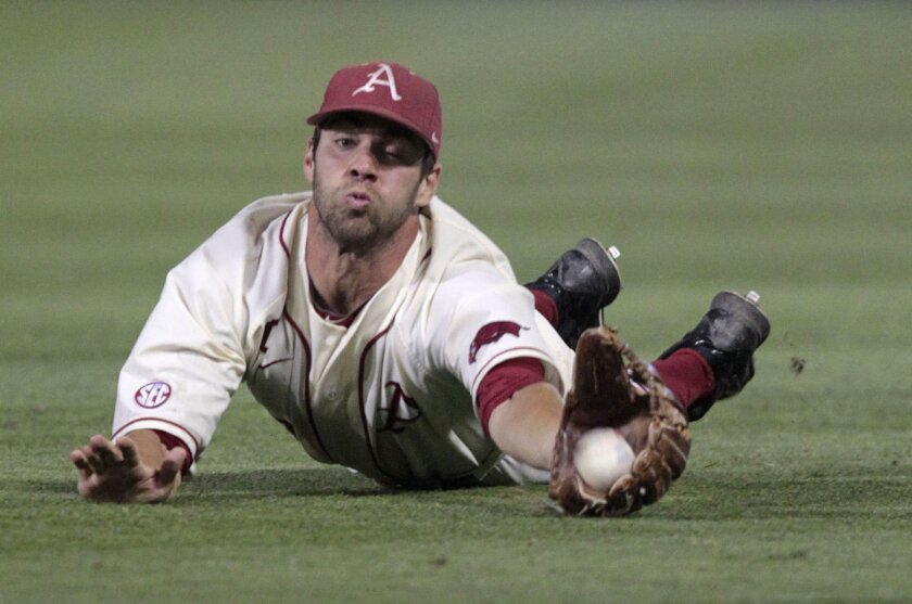 Arkansas outfielder Tyler Spoon (8) makes a diving catch in the sixth inning during an NCAA college baseball regional tournament game against Virginia in Charlottesville, Va., Sunday, June 1, 2014. (AP Photo/Andrew Shurtleff)