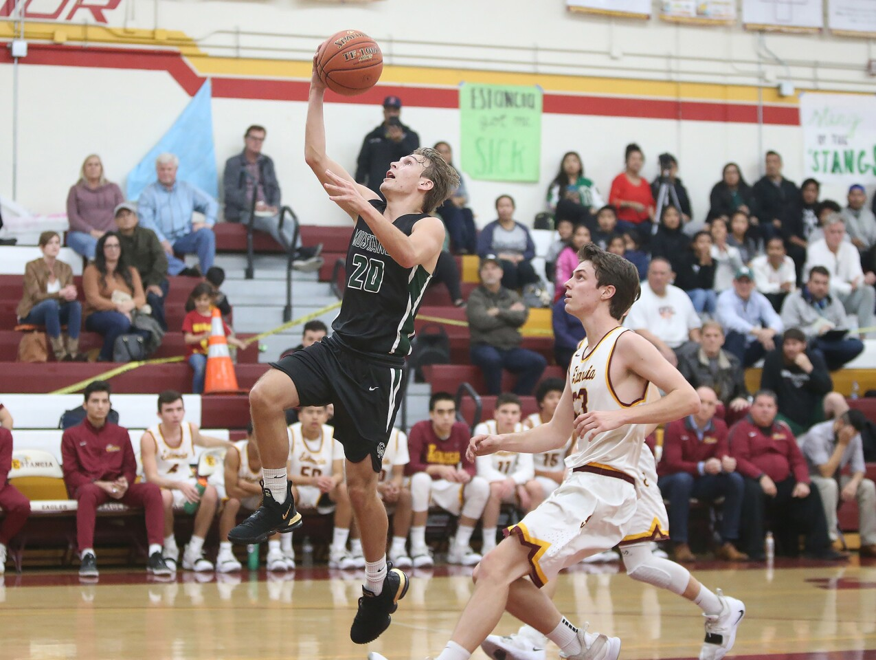 Costa Mesa High's Osman Hefner (20) drives in for a layup as Estancia's Jake Covey watches during an Orange Coast League boys' basketball game on Wednesday.