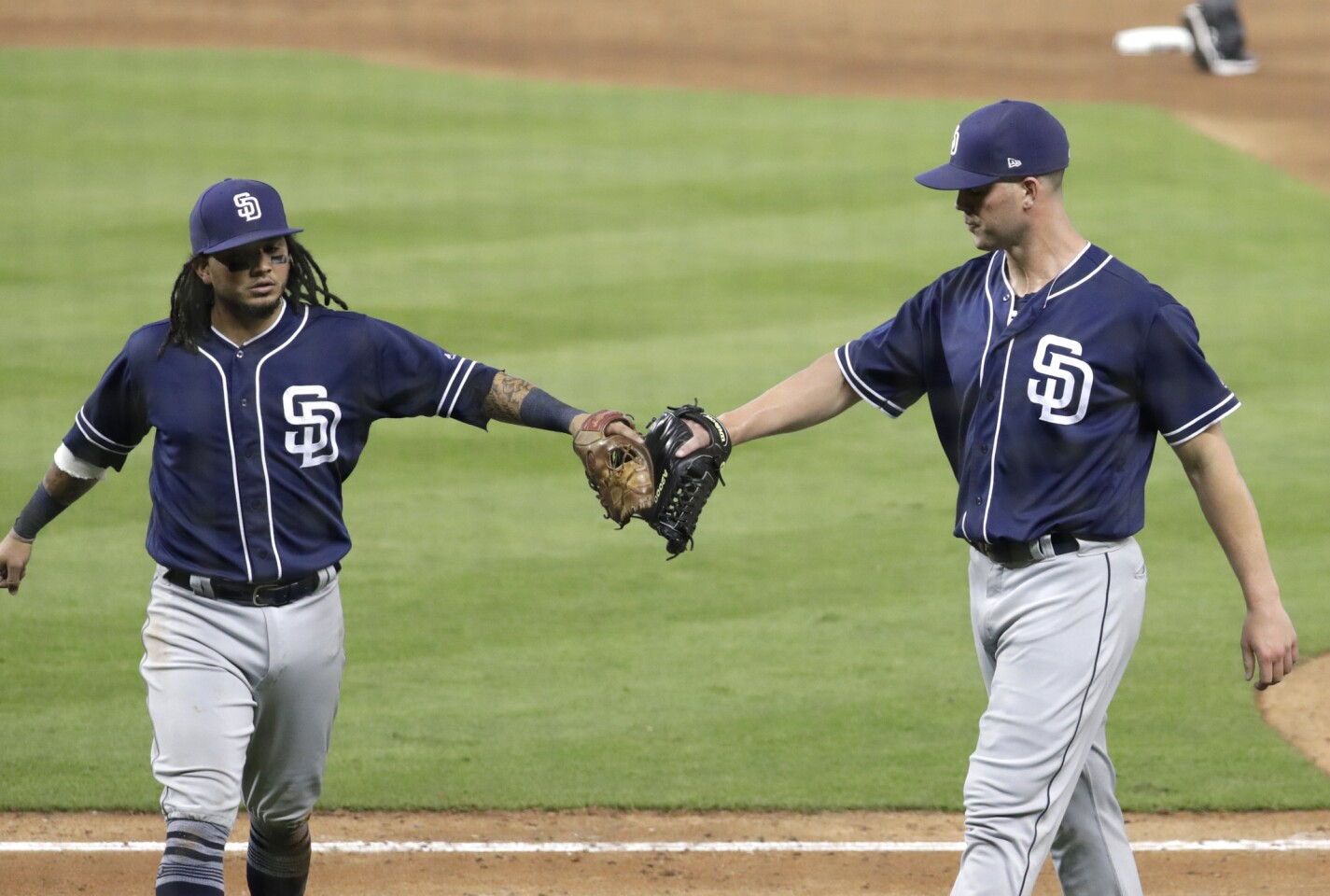 San Diego Padres starting pitcher Clayton Richard, right, bumps fists with San Diego Padres shortstop Freddy Galvis after losing a no-hit bid when Miami Marlins' Miguel Rojas hit a single during the seventh inning of a baseball game, Sunday, June 10, 2018, in Miami. The Padres won 3-1. (AP Photo/Lynne Sladky)