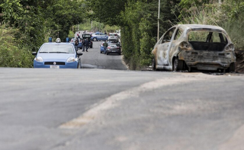 The burned car belonging to slain 22-year-old student Sara Di Pietrantonio is seen along a street in the outskirts of Rome, Monday, May 30, 2016. According to Italian police, Sara, who's body was found close to the car, has been burned alive by her ex-boyfriend as she was was trying to escape from