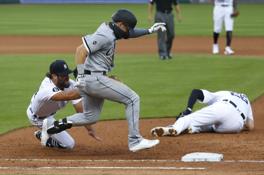 Detroit Tigers pitcher Daniel Norris, left, dives to tag out Chicago White Sox's Danny Mendick, center, as first baseman C.J. Cron (26) lies injured on the field in the fourth inning of a baseball game in Detroit, Monday, Aug. 10, 2020. (AP Photo/Paul Sancya)