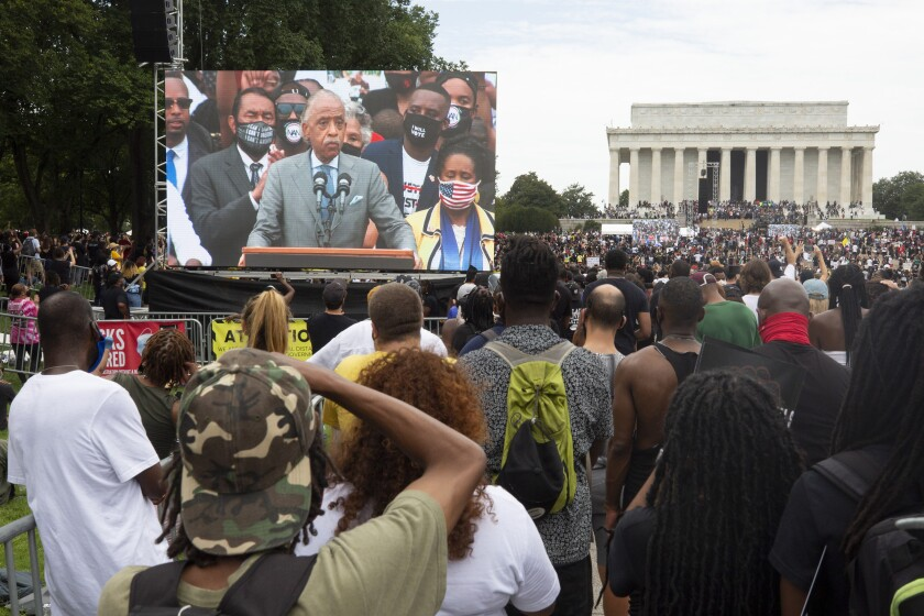"""Rev. Al Sharpton speaks to protesters during a rally for the National Action Committee """"Get Your Knee Off Our Necks""""."""
