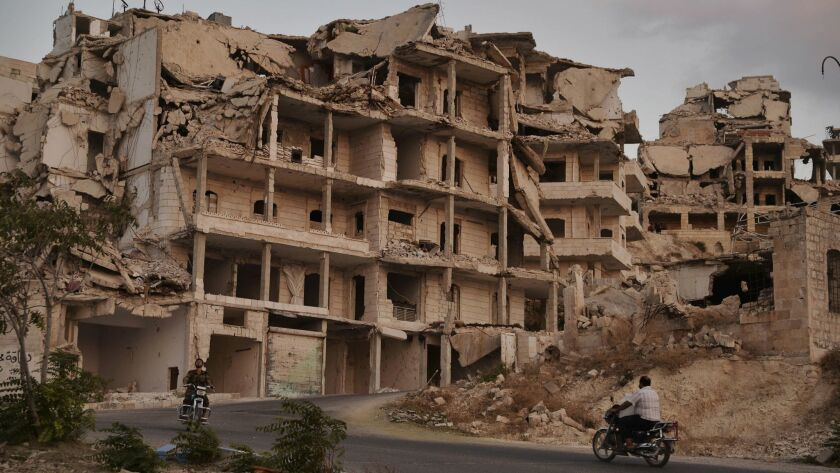 Motorcyclists ride past buildings destroyed during fighting in the northern town of Ariha, in Idlib province, Syria.