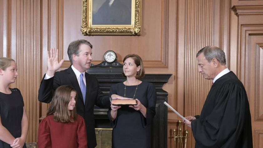 Chief Justice John G. Roberts Jr. administers the constitutional oath on Oct. 6 to Brett Kavanaugh, accompanied by his wife and daughters.