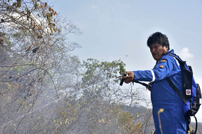 """FILE - In this Aug. 27, 2019 file photo courtesy of Bolivia's Communication Ministry press office, Bolivian President Evo Morales sprays water on a fire burning on the outskirts of Robore, Bolivia. Memes have gone viral in Bolivia showing Morales combatting forest fires with a toy water gun or a flame-thrower, while others superimpose his image on the original cast of the """"Ghostbusters"""" film, as a way to poke fun at South America's longest-serving leader and his delayed response to forest fires. (Raul Martinez/Bolivia's Communication Ministry press office via AP, File)"""