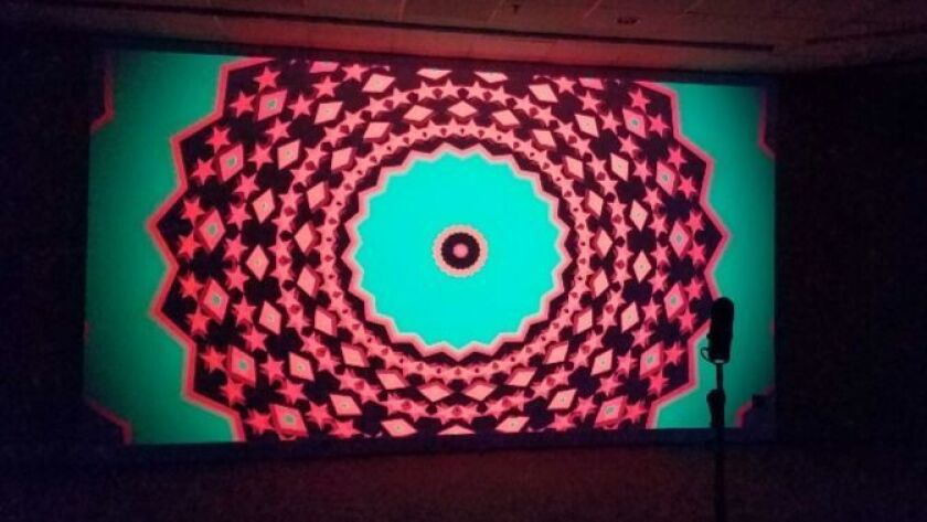 A microphone stand in front of Hank Willis Thomas' psychedelic video projection invites visitor participation.