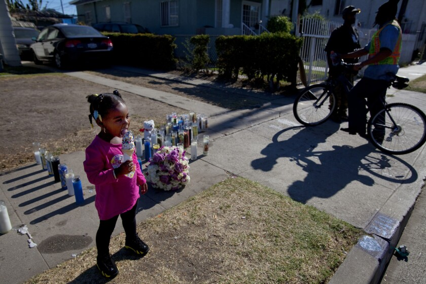 Aubriel Turner, 2, eats an ice cream cone Wednesday near candles placed on the sidewalk in remembrance of her cousin, Ezell Ford, who was killed by Los Angeles police officers in the 200 block of West 65th Street.