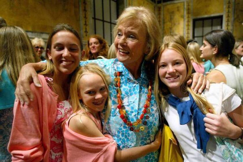 Fashion designer Lilly Pulitzer receives hugs of support from her granddaughters, Lilly, left, Charlotte and Emma in 2002 after presenting her spring collection at the New York Public Library. It was her first time presenting her collection at a fashion show.