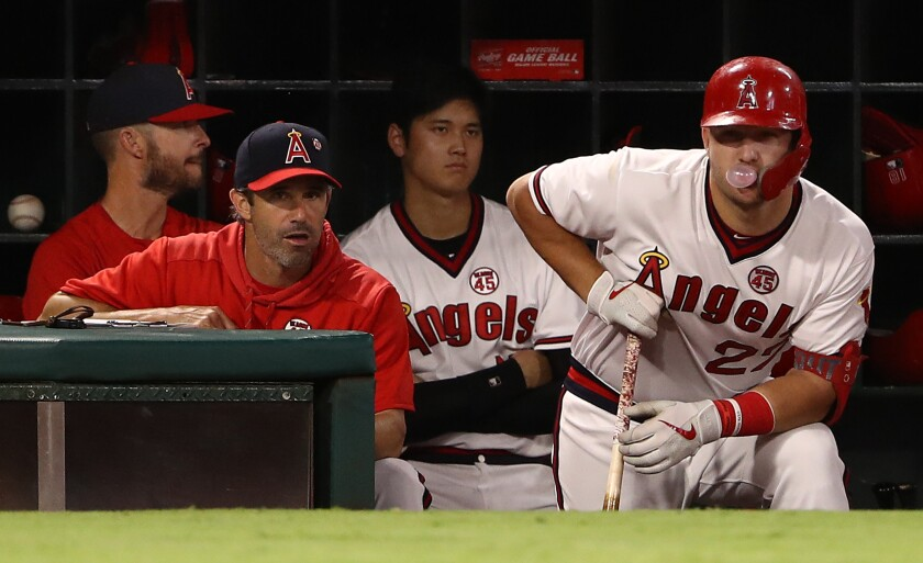 Angels manager Brad Ausmus stands next to slugger Mike Trout during a game against the Chicago White Sox in August.