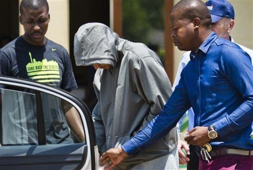 Olympic athlete Oscar Pistorius leaves the Boschkop police station, east of Pretoria, South Africa, Thursday, Feb. 14, 2013. Pistorius was taken into custody after a 30-year-old woman, Reeva Steenkamp, was shot dead at his home. (AP Photo)