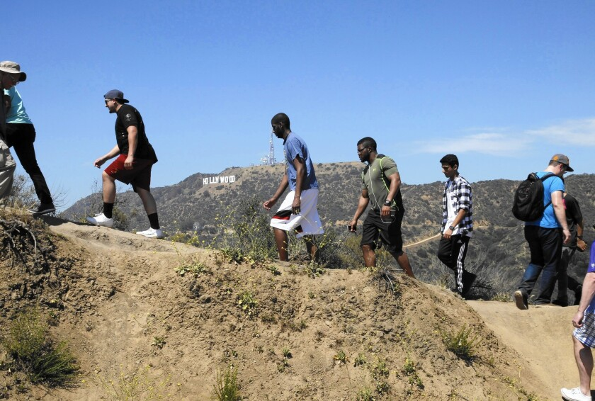 Tourists take a short hike to photograph the Hollywood sign in Griffith Park.