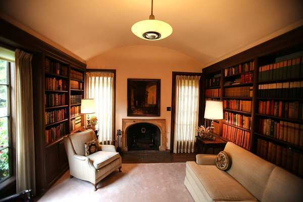Wood bookshelves, detailed in the Winter House's original blueprints, line either side of the barrel-ceilinged library, and a fireplace with a tile-surround is flanked by tall windows.