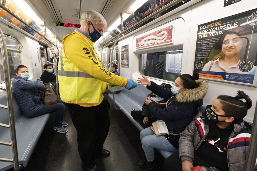 A man in a yellow MTA shirt and vest hands out masks to riders on a New York City subway