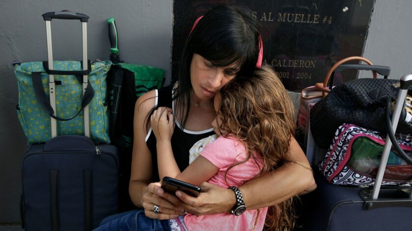 After eight hours in line, Solymar Duprey, 47, holds her daughter Miabella Lawston, 5, as they try t