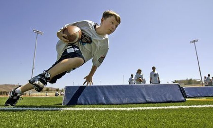 Randy Robbins practiced his cornering footwork and ball protection at yesterday's Darren Sproles Powered Up Youth Football Camp at Del Norte High School in 4S Ranch. Randy was among 132 youths who took part.  (Nelvin C. Cepeda / Union-Tribune)