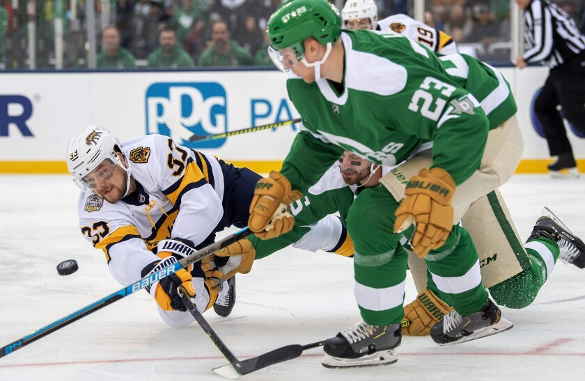 Nashville Predators right wing Viktor Arvidsson (33) dives to the ice as he competes for the puck with Dallas Stars defenseman Esa Lindell (23) and left wing Blake Comeau in the first period of the NHL Winter Classic hockey game at the Cotton Bowl, Wednesday, Jan. 1, 2020, in Dallas. (AP Photo/Jeffrey McWhorter)