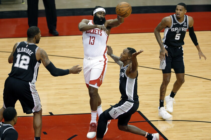 Houston Rockets guard James Harden (13) passes the ball over San Antonio Spurs forward LaMarcus Aldridge (12), guards Lonnie Walker IV, middle right, and Dejounte Murray (5) during the first half of an NBA basketball game Tuesday, Dec. 15, 2020, in Houston. (AP Photo/Michael Wyke)
