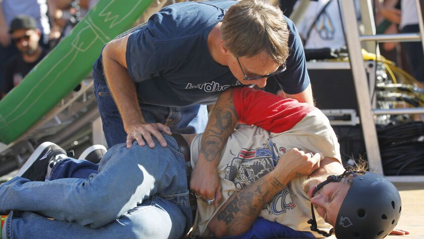 Tony Hawk checks on his son, Riley, who fell attempting the Loop Challenge Live in Vista on Suunday.