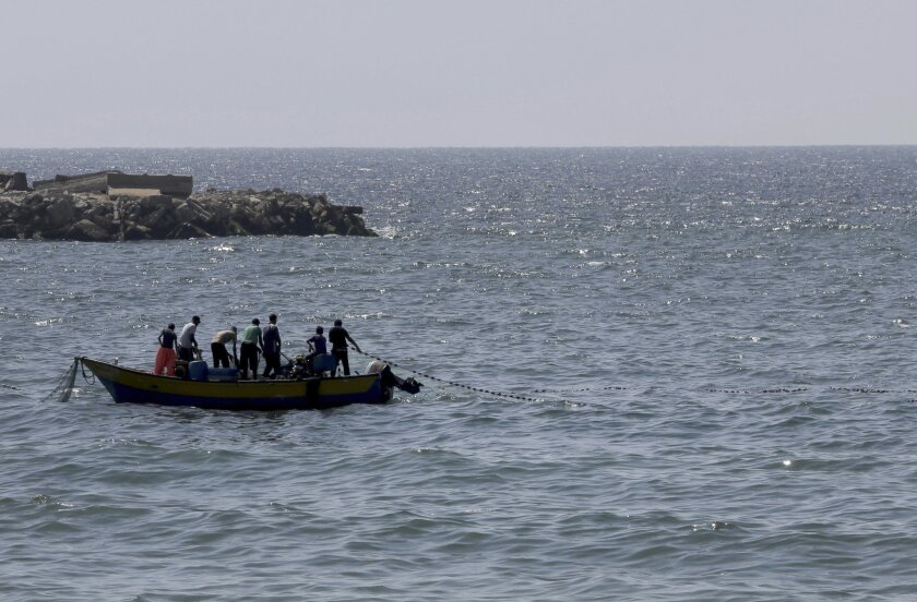 Palestinian fishermen pull their fishnet at the Mediterranean Sea in Gaza City in the northern Gaza Strip on Thursday, Aug. 7, 2014. (AP Photo/Adel Hana)