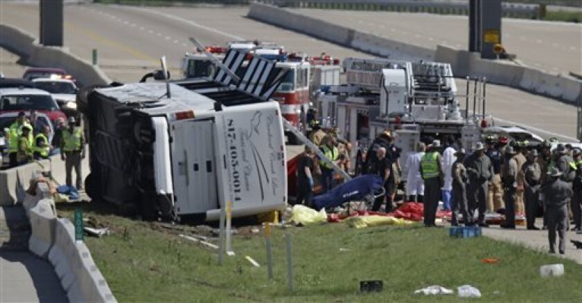A fatality is rolled away as emergency responders works the scene of  bush crash on the George Bush Turnpike Thursday, April 11, 2013, in Irving, Texas. The chartered bus overturned on the busy highway near Dallas on killing at least two people and injuring several others, authorities said. (AP Pho