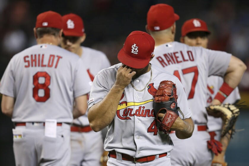 St. Louis Cardinals relief pitcher Junior Fernandez, right, walks back to the dugout after being taking out of the baseball game by manager Mike Shildt (8) after giving up four runs against the Arizona Diamondbacks during the sixth inning Wednesday, Sept. 25, 2019, in Phoenix. (AP Photo/Ross D. Franklin)