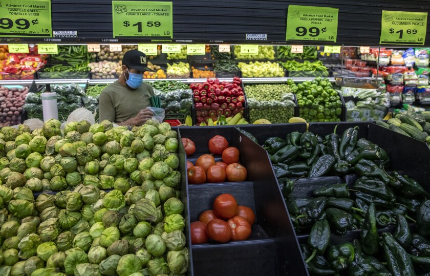 A shopper wears a mask to guard against the coronavirus as he picks out produce items at the Advance Food Market on Saturday, April 4, 2020 in West Adams, CA.