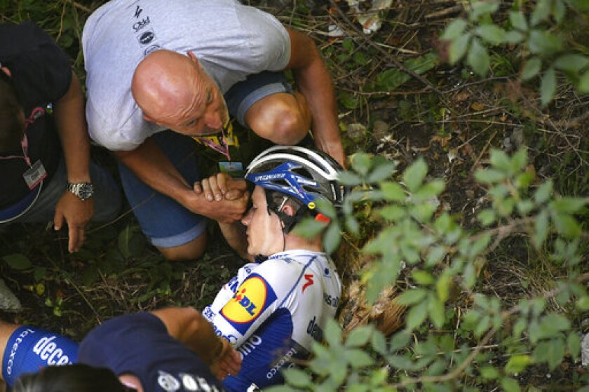 Cyclist Remco Evenepoel receives first aid after falling during the Tour of Lombardy cycling race, from Bergamo to Como, Italy, Saturday, Aug. 15, 2020. (Fabio Ferrari/LaPresse via AP)