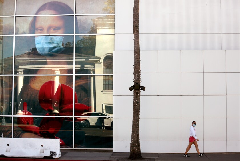 A masked pedestrian walks past a large depiction of Mona Lisa wearing a mask in a building's window