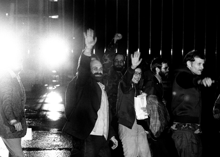 Barry Rosen, left, and other U.S. hostages wave to media as they arrive at Algiers airport from Tehran on Jan. 21, 1981.