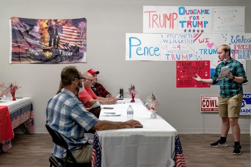 Ryan Retza (der) da instrucciones a voluntarios en una unidad de apoyo a Donald Trump