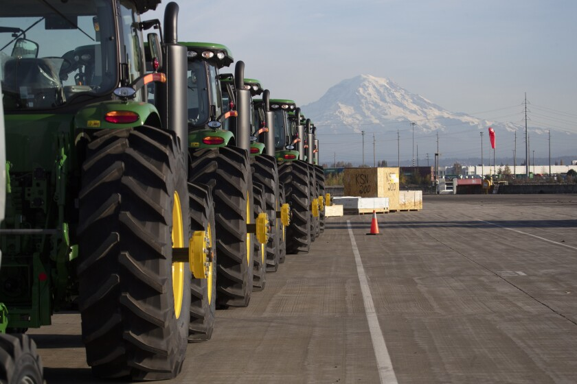 FILE - In this Nov. 4, 2019 file photo, John Deere tractors made by Deere & Company are shown as they are readied for export to Asia at the Port of Tacoma in Tacoma, Wash. The U.S. trade deficit fell in September 2020 after hitting a 14-year high in August as exports outpaced imports. The Commerce Department reported, Wednesday, Nov. 4, 2020, the gap between what the U.S. sells and what it buys abroad fell to 63.9 billion in September, a decline of 4.7% from a $67 billion deficit in August. (AP Photo/Ted S. Warren, File)