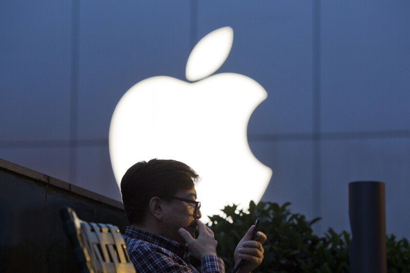 A man uses his mobile phone near an Apple store logo in Beijing, China on Friday, May 13, 2016. The company is being sued by a subsidiary of China's broadcasting regulator over a propaganda film more than 20 years old.