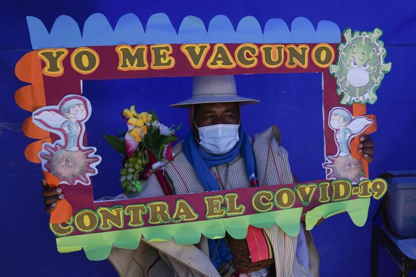 Un residente sostiene un marco con un mensaje mientras posa para una foto durante una campaña de vacunación dirigida a la comunidad indígena Uru Chipaya, en Chipaya, Bolivia, el viernes 23 de julio de 2021. (AP Foto/Juan Karita)
