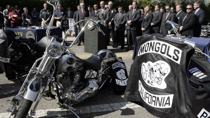 Law enforcement officials announce the arrests of dozens of members of the Mongols motorcycle club in 2008. In a current racketeering case, federal prosecutors want the club to forfeit the trademark it has on its insignia, which is seen on the jacket.