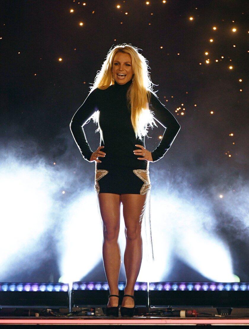 Britney Spears stands on a stage while wearing a minidress.