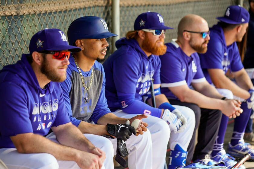 Dodgers teammates (from left) Max Muncy, Mookie Betts, and Justin Turner sit in the dugout during a spring training practice session Feb. 20.